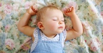 Miért alszik a baba feltartott kezekkel?